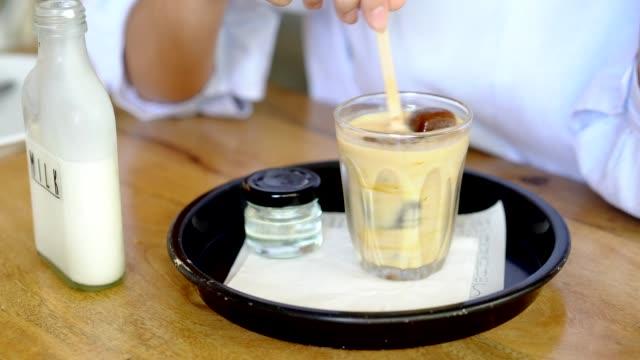 stockvideo's en b-roll-footage met vrouw maken iced koffie met melk in glazen en drinken. - koffie drank