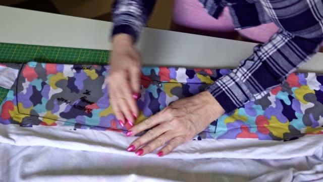 vídeos y material grabado en eventos de stock de mujer haciendo pantalones en un patrón - una mujer de mediana edad solamente