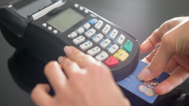 woman making payment with credit card and entering pin code - credit card stock videos and b-roll footage