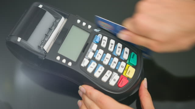 Woman making payment with credit card and entering PIN code