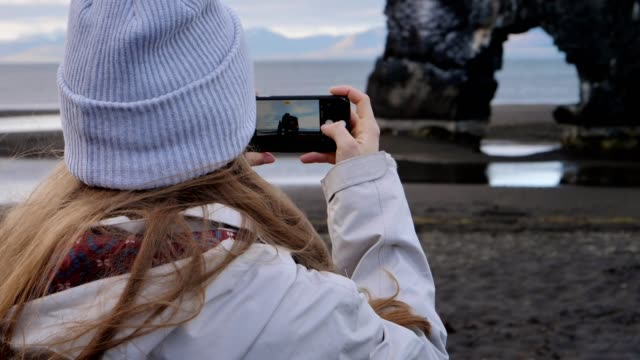 woman making photo of famous sea stack - femininity photos stock videos & royalty-free footage