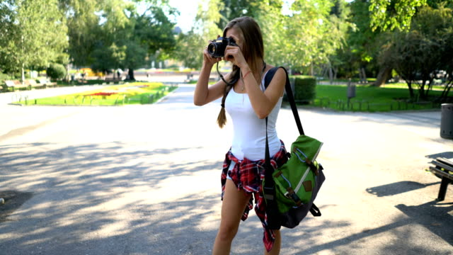 woman making photos in the park - photographing stock videos and b-roll footage