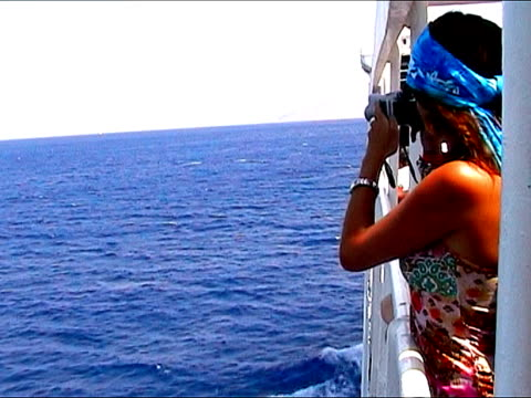 vídeos de stock e filmes b-roll de mulher fazendo fotografias a partir de um navio, - embarcação comercial
