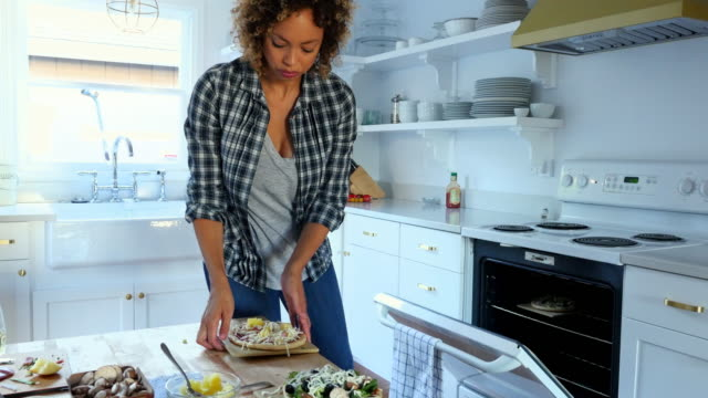 MS Woman making pizzas in kitchen of home