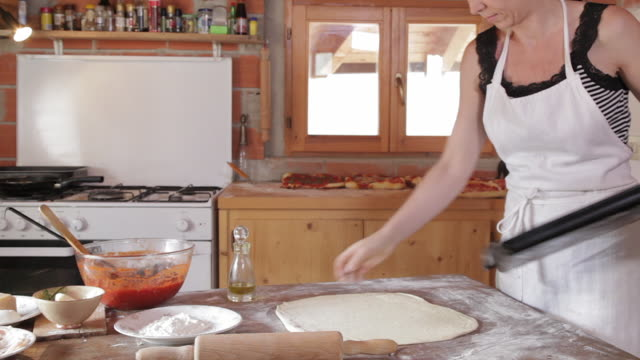 Woman making pizzas in kitchen of home