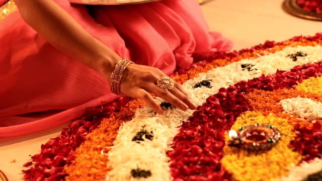 CU Woman making rangoli of flowers on diwali festival