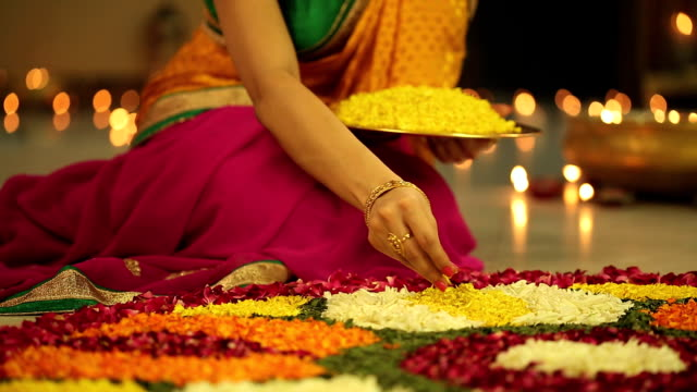 MS Woman making rangoli with petals during in diwali festival