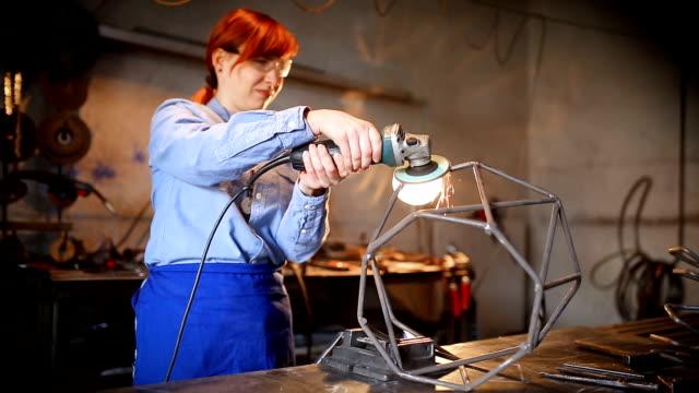 vidéos et rushes de femme faisant la sculpture à l'aide d'outil de broyage - fer