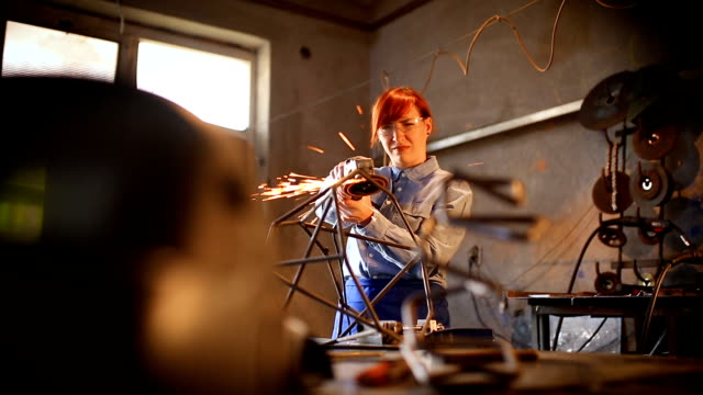 Woman making sculpture using grinding tool