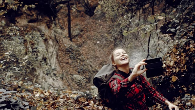 Woman making selfie in autumnal forest
