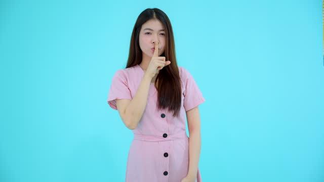 la donna che fa un gesto di zitto non fare rumore forte o tacere su uno sfondo blu isolato - silenzio video stock e b–roll