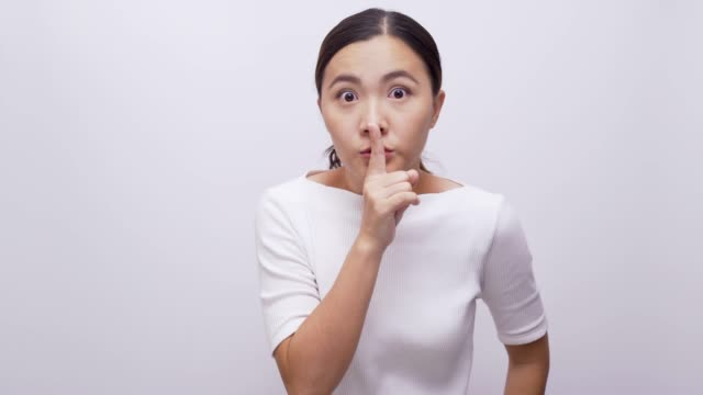 woman making shush gesture on isolated white background 4k - displeased stock videos and b-roll footage