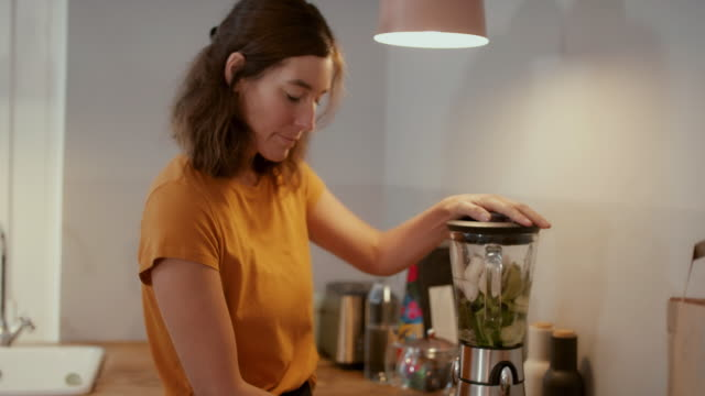 woman making smoothie in blender at home - kitchen worktop stock videos & royalty-free footage