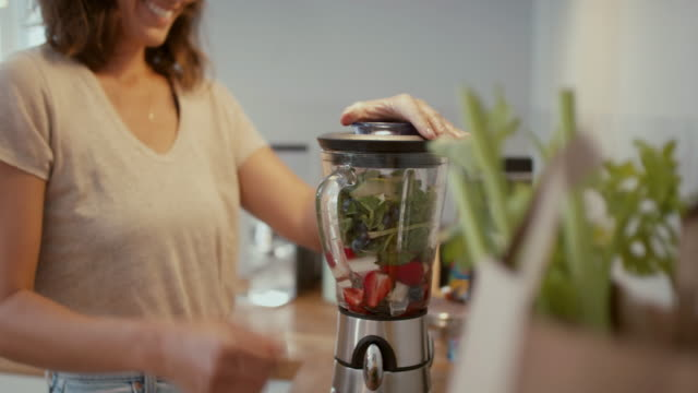woman making smoothie in kitchen at home - mixer stock-videos und b-roll-filmmaterial