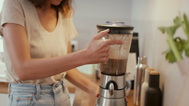 woman making smoothie in kitchen at home - vorbereitung stock-videos und b-roll-filmmaterial