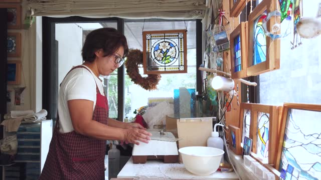 a woman making stained glass in her home studio - cut video transition stock videos & royalty-free footage