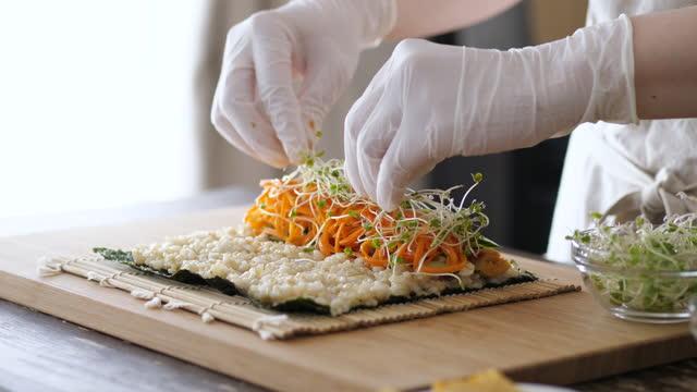 寿司巻きを作る女性。 - 玄米点の映像素材/bロール