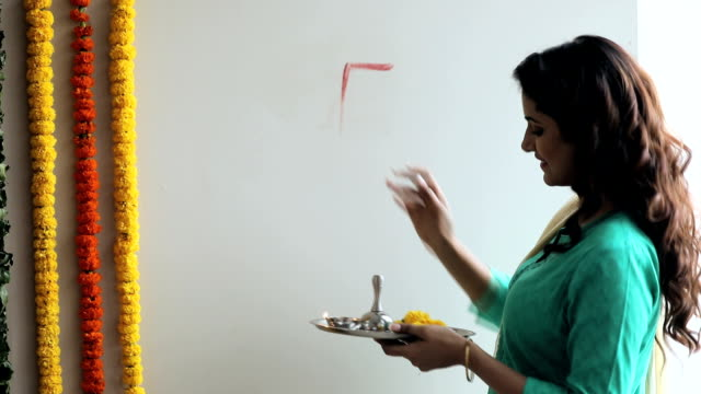 vídeos y material grabado en eventos de stock de woman making swastika design on house wall, delhi, india - bandeja para servir