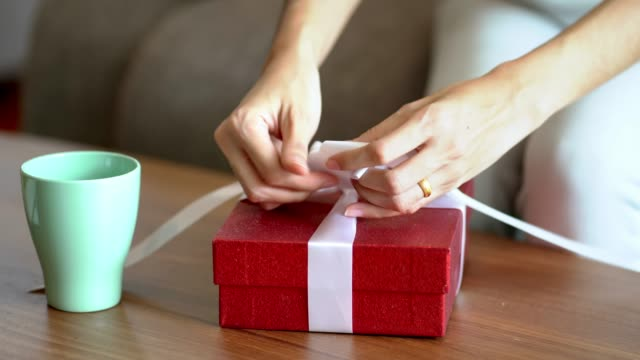 woman making the package red gift box with white ribbon. - wrapped stock videos & royalty-free footage
