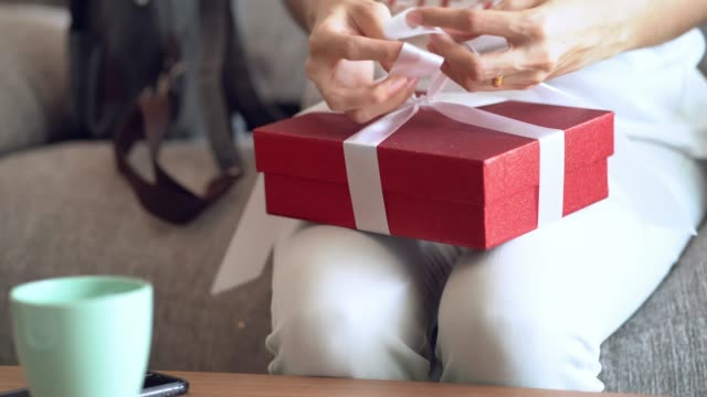 woman making the package red gift box with white ribbon. - gift stock videos & royalty-free footage