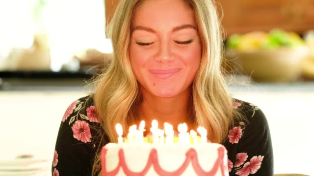 vídeos de stock e filmes b-roll de woman making wish and blowing out candles on birthday cake - soprar