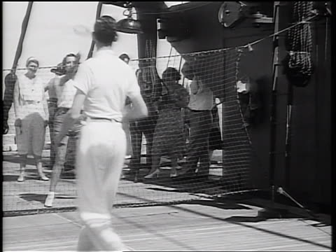 "b/w 1934 woman + man playing ""deck tennis"" with ring over net on ship deck / people watching in background - 1934 stock-videos und b-roll-filmmaterial"
