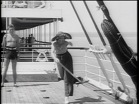 vídeos de stock, filmes e b-roll de b/w 1934 woman + man with bathing suit playing shuffleboard on ship deck / ocean in background - 20 anos