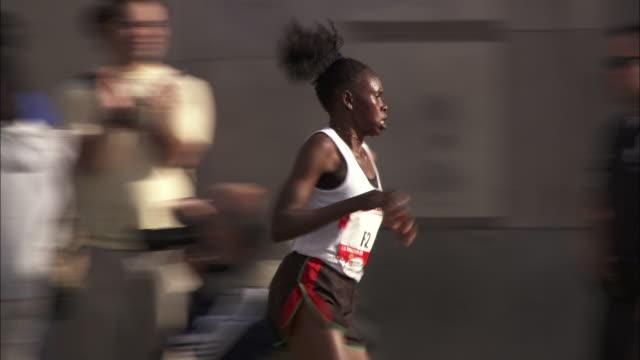 vídeos de stock, filmes e b-roll de a woman marathoner runs past spectators on a city street. - maratona