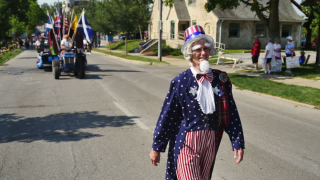 A woman marches while dressed as Uncle Sam during the 4th of July parade in Bloomington Indiana