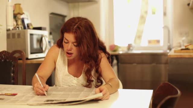 woman marking job advertisements in newspaper - 職探し点の映像素材/bロール