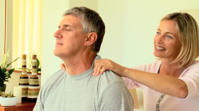 vidéos et rushes de woman massaging her husband's shoulders / cape town, western cape, south africa - mari