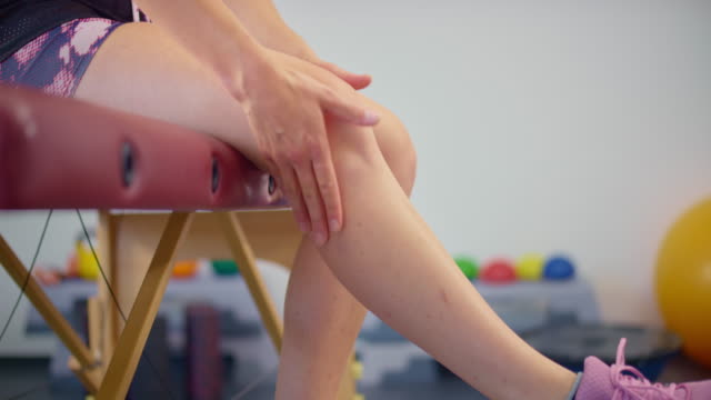 slo mo woman massaging her leg because of the pain - massage table stock videos & royalty-free footage