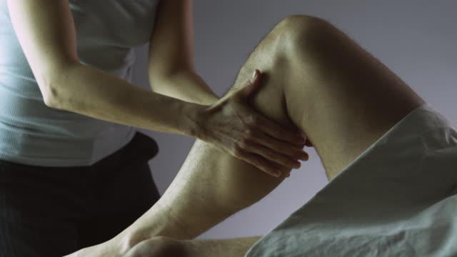 SLO MO MS Woman massaging men's leg in studio / New York City, New York State, USA