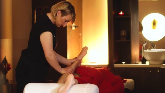 vidéos et rushes de femme masser les jambes de l'autre femme - massage table