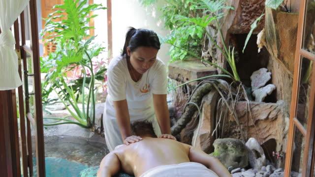 vídeos de stock e filmes b-roll de ms woman massaging woman in massaging parlour of gaia oasis resort, tejakula, bali, indonesia - massagem