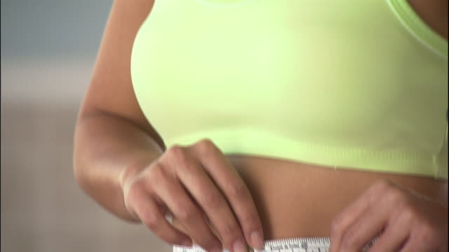 a woman measures her waist with a measuring tape. - waist stock videos & royalty-free footage