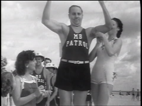 b/w 1937 woman measuring bicep of male lifeguard in beauty contest / florida / newsreel - beauty contest stock videos & royalty-free footage