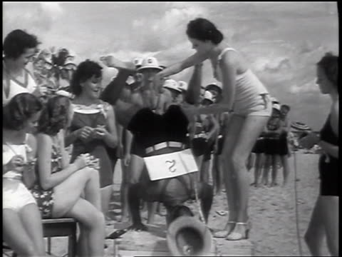 b/w 1937 woman measuring calves of lifeguard doing handstand in beauty contest / florida / newsreel - beauty contest stock videos & royalty-free footage