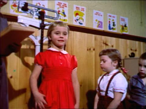 1957 woman measuring children's height in classroom / new jersey / industrial - 測る点の映像素材/bロール
