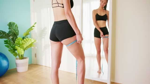 彼女の太ももを測定する女性 - 低炭水化物ダイエット点の映像素材/bロール