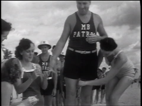 b/w 1937 woman measuring thighs of lifeguard in beauty contest as he flirts with other women / florida - beauty contest stock videos & royalty-free footage