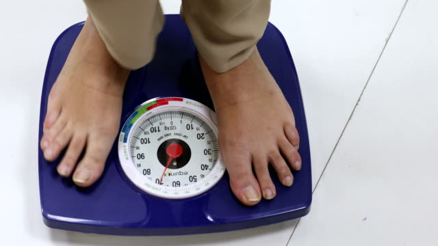 woman measuring weight, delhi, india - waage gewichtsmessinstrument stock-videos und b-roll-filmmaterial