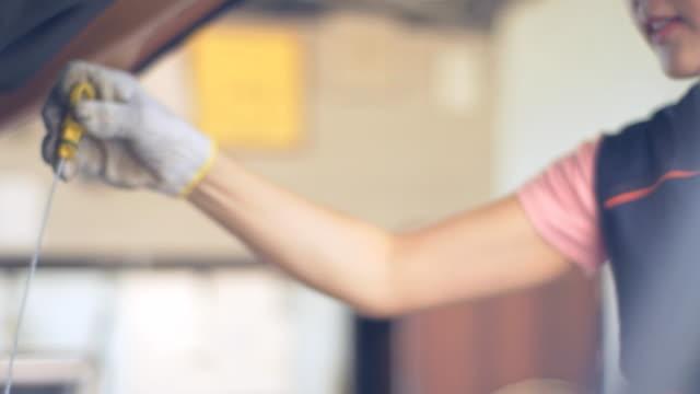 vídeos de stock, filmes e b-roll de mulher mecânica verificando um carro - motor