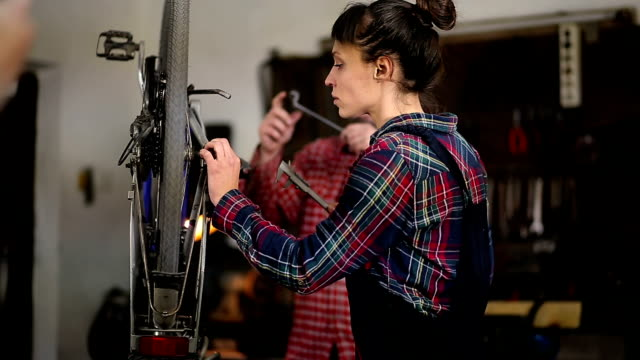 Woman Mechanic is Repairing Bike In Workshop, And Craftsman Assisting