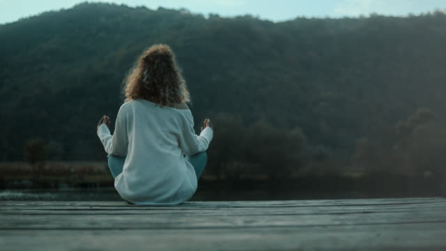 woman meditateing on pier on lake - pier stock videos & royalty-free footage