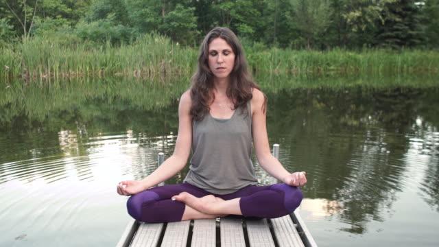 woman meditates on a dock - 胡坐点の映像素材/bロール