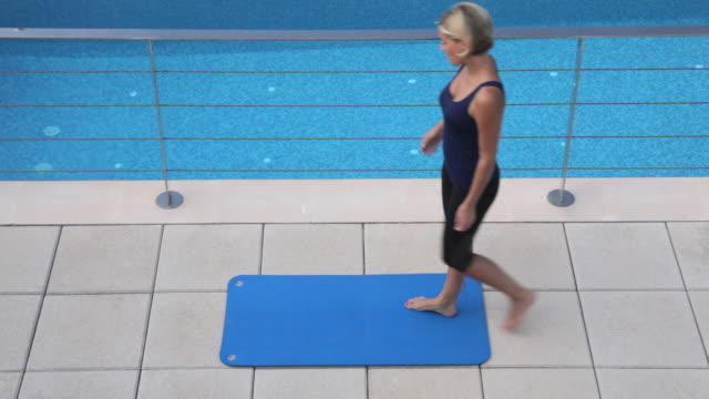 ha woman meditating at poolside,mallorca - korslagda ben bildbanksvideor och videomaterial från bakom kulisserna