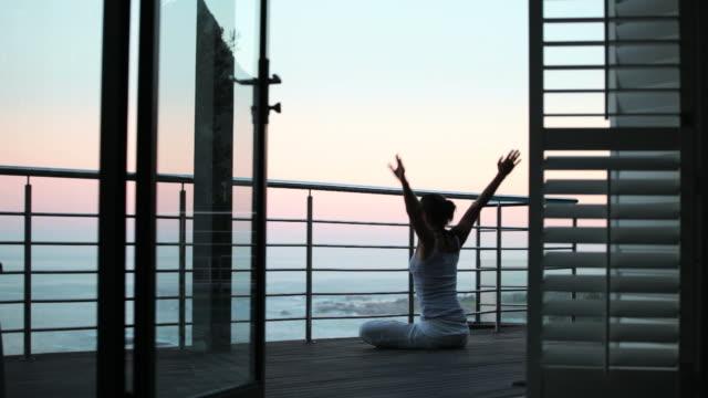 vídeos de stock, filmes e b-roll de mulher meditating ao nascer do sol - varanda