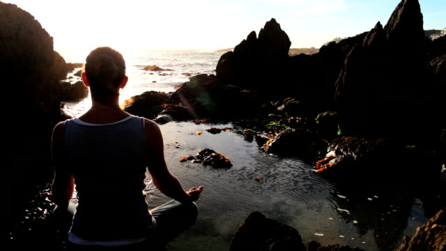 woman meditating at sunset - lotus position stock videos & royalty-free footage
