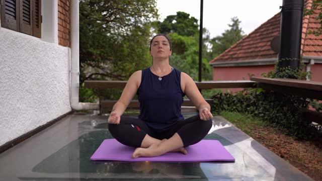 stockvideo's en b-roll-footage met vrouw die yoga thuis doet - lotuspositie